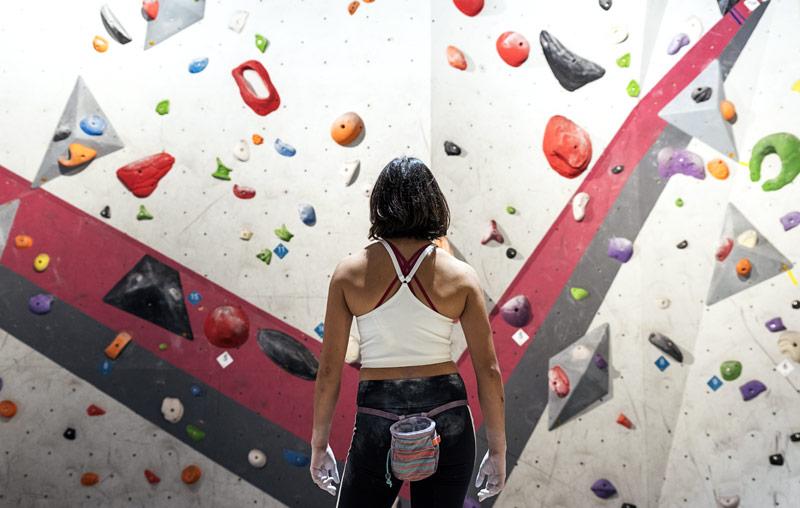 ボルダリングの壁の前に立つ女性