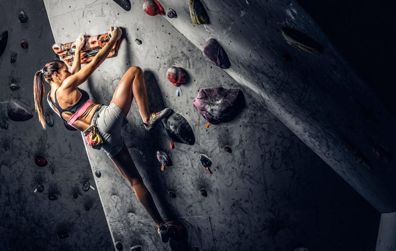 クライミングホールドに足をかける女性